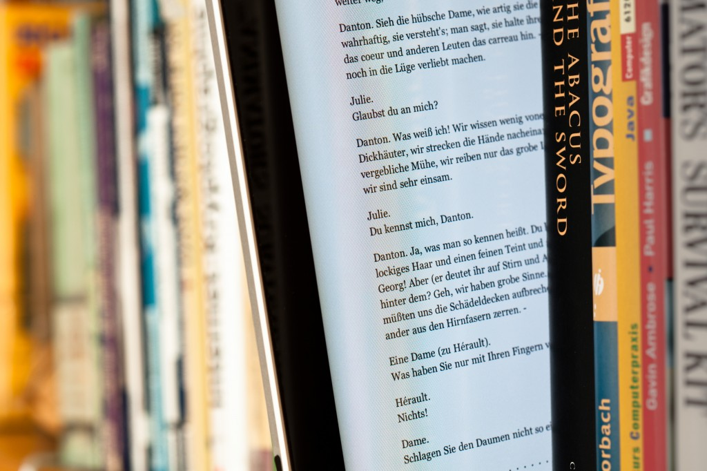 Photo of an ebook reader amongst print books